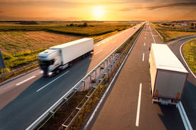 picture of trucks  - Two trucks on highway in motion blur at sunset - JPG