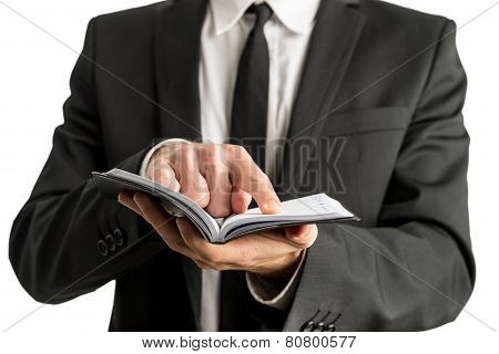 Closeup Of A Businessman Holding Small Notebook Or Planner