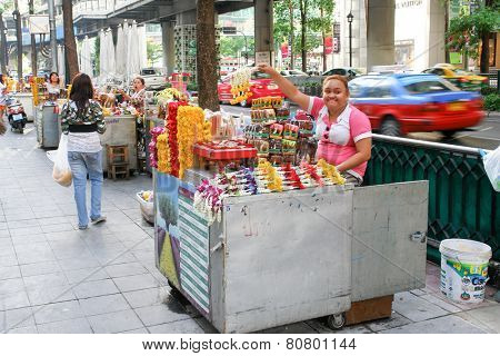 BANGKOK, THAILAND - MARCH 22, 2009: Thai flower vendor sells  Buddhist flowers on the street.