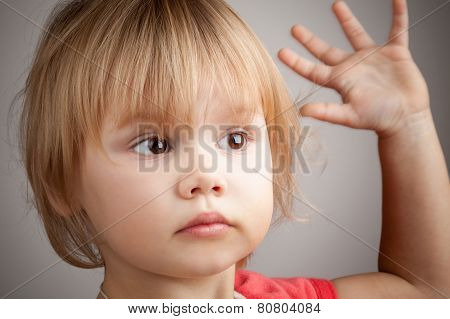 Portrait Of Cute Blond Baby Girl With Hand Up Gesture