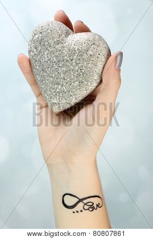 Female arm with tattoo holding decorative heart on light background