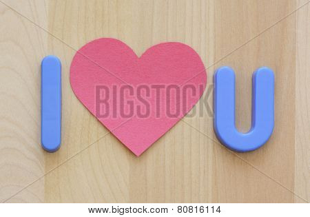 Close up of I love U in plastic blue toy letters and empty flat pink heart shape paper