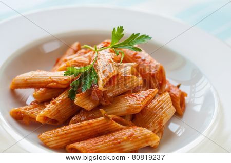 Close up of cooked penne pasta in tomato sauce.
