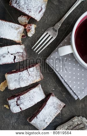 Cherry And Walnut Strudel On A Dark Wooden  Table. Closeup