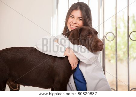 Cute Veterinarian Hugging A Dog