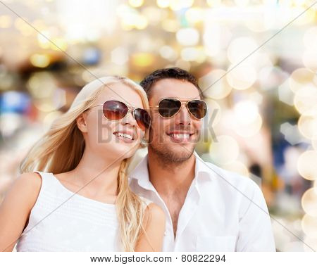 summer holidays, people and dating concept - happy couple in shades over lights background