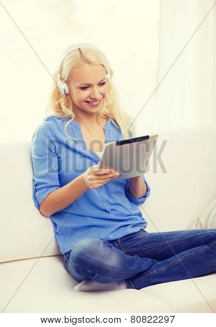 home, music, technology and internet concept - smiling woman sitting on the couch with tablet pc computer and headphones at home