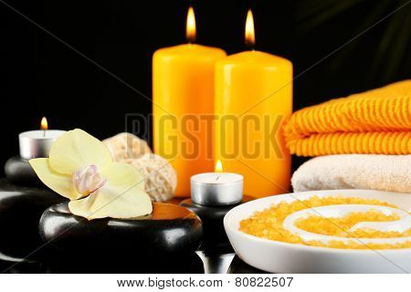 Beautiful spa composition with candles and orchid on dark background
