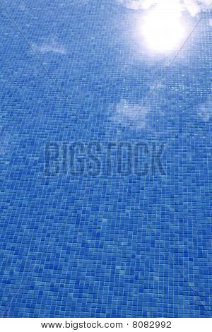 Blue Tiled Swimming Pool With Sun Reflexion