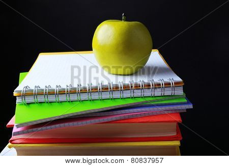 School supplies and apple on black background