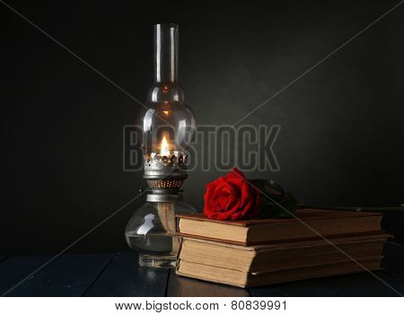 Kerosene lamp with books and red rose on wooden table and dark background