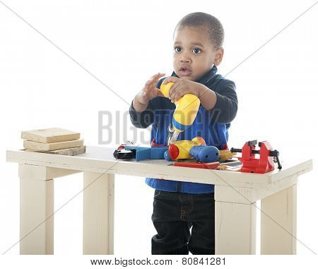 An adorable toddler drilling with a toy