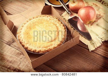 Closeup of a fresh apple pie in a bakery box on a rustic wood table. A plate, serving utensil and fresh Fuji apples are in the background. Horizontal format with instagram effect applied.
