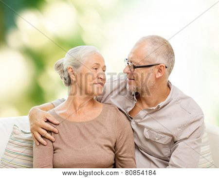 family, relations, love, age and people concept - happy senior couple hugging and looking at each other on sofa over green background