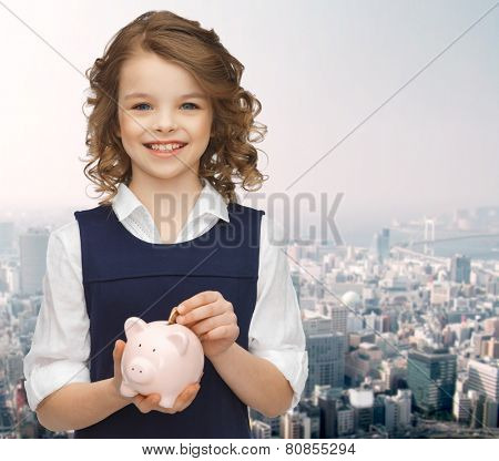 people, money, savings, investment and children concept - smiling girl putting coin into piggy bank over city background