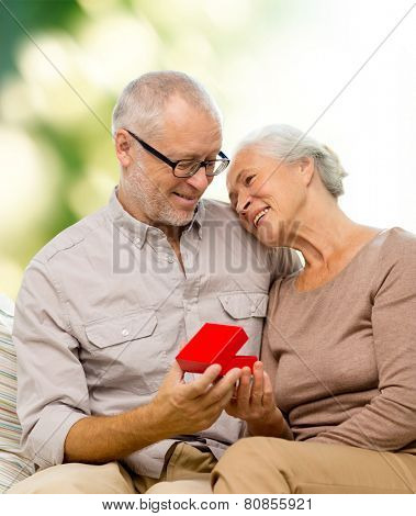 family, holidays, age and people concept - happy senior couple with little red gift box over green background