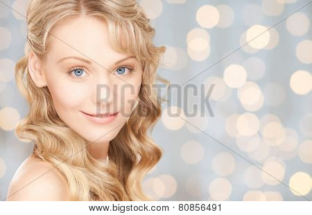 people, beauty, body and skin care concept - beautiful woman face and hands over holidays lights background