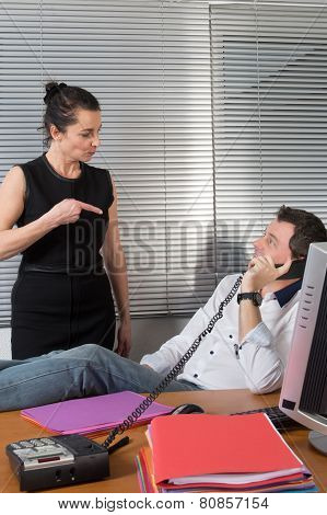 Business Man Relaxing At Office Desk And Talking On Mobile Phone