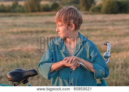 Portrait of teenager boy with bicycle at sunset