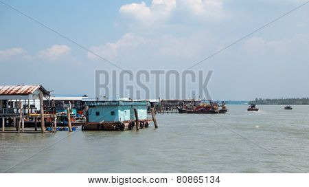 PULAU KETAM, MALAYSIA - JANUARY 18, 2015: Traditional Malay fishing boats ply the sea around the fisherman's wharf after return from sea. This island is famous for sea food products and restaurants.