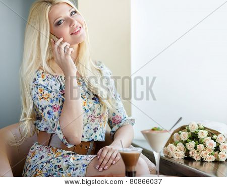 Beautiful woman at a table in a café with a mobile phone.