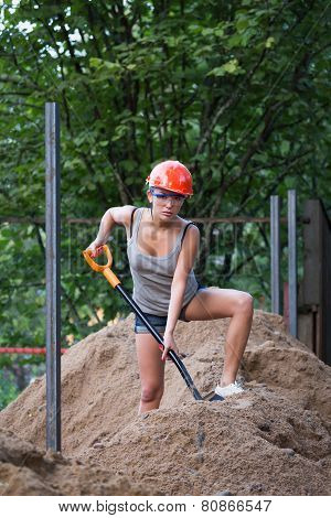 Pretty Young Woman Builder Digging A Shovel