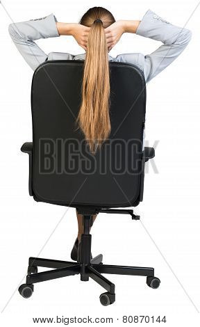 Businesswoman sitting back in office chair with hands clasped behind her head. Back view