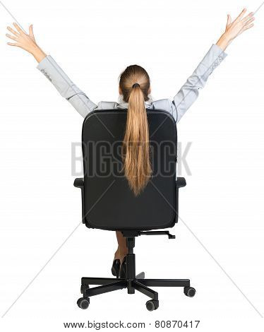 Businesswoman stretching in the chair of her office. Back view
