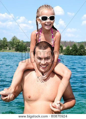 Smiling Little Girl Sitting On Father's Shoulders