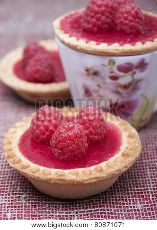 Tartlets Of Shortcrust Pastry With Raspberry Jelly And With Raspberry On Plate And  On Cup  .