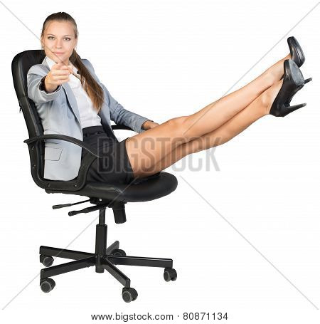 Businesswoman on office chair with her feet up, pointing finger at camera