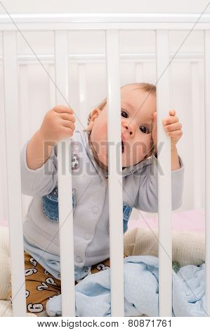 baby biting the bars bed