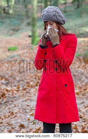 Young woman suffering from a cold or flu blowing her nose on a white paper handkerchief on a forest wearing a red overcoat, a beanie and gloves during winter