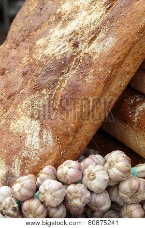Close up of rustic bread and bulbs of fresh garlic
