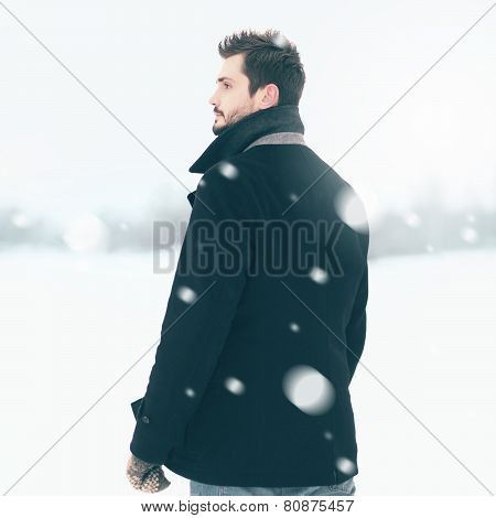 Handsome Elegant Man Standing Outdoors In The Winter Blizzard And Looks Into The Distance