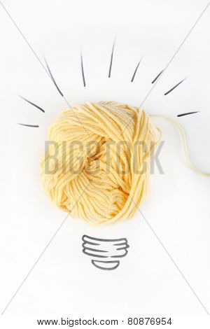 Symbol of idea as light bulb on sheet of paper from skein of thread, isolated on white