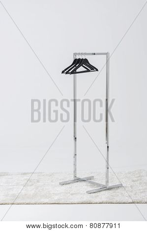 Simple Metal Clothing Rail With Empty Coat Hangers