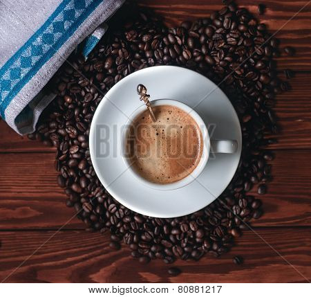 Coffee cup with burlap sack of roasted beans against dark wood background
