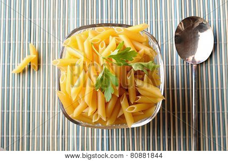Uncooked Macaroni In A Bowl On A Bamboo Tablecloth Top View
