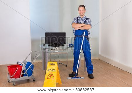 Confident Male Janitor With Cleaning Equipments
