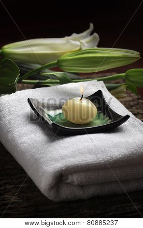 Burning scented candle placed on white towel.