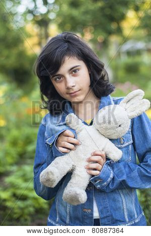 Young cute girl in a denim jacket with an old toy, outdoors.