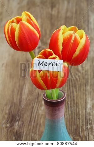 Merci card (which means thank you in French) with red and yellow tulips