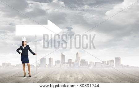 Young businesswoman in paper crown carrying blank banner. Place for text