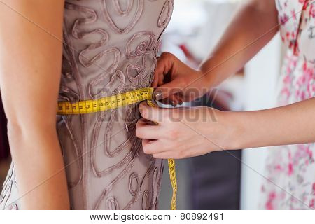 Pretty dressmaker at work making measures of client