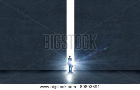 Rear view of businessman standing in light of way in wall