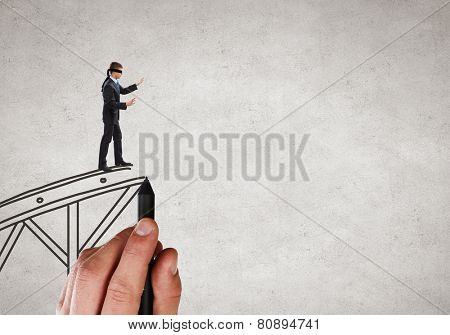 Businessman in blindfold walking on drawn bridge over gap