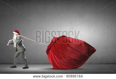 Businessman in Santa hat pulling big red bag