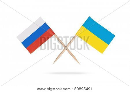 Crossed mini flags Russia and Ukraine with shadow below. Isolated on white background
