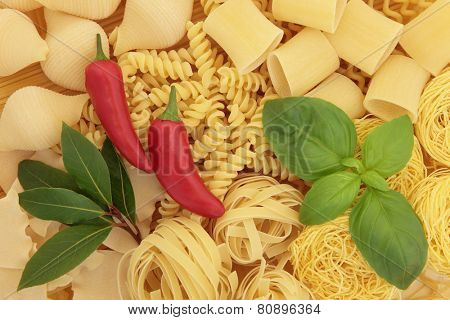 Italian pasta food with basil, bay leaf herbs and chili spice forming an abstract background.